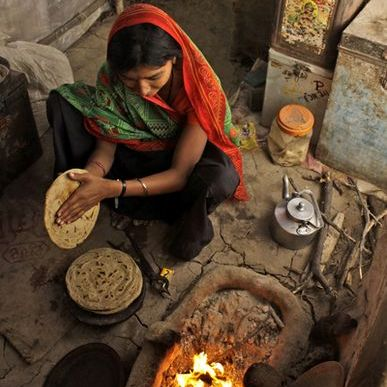 Lady making rôti on a floor stove in Western Gujarat - India.